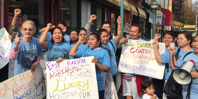 "Group of people at a rally held by Movement for Justice in El Barrio, holding signs saying things like ""East Harlem Against De Blasio's Luxury Housing Plan"""
