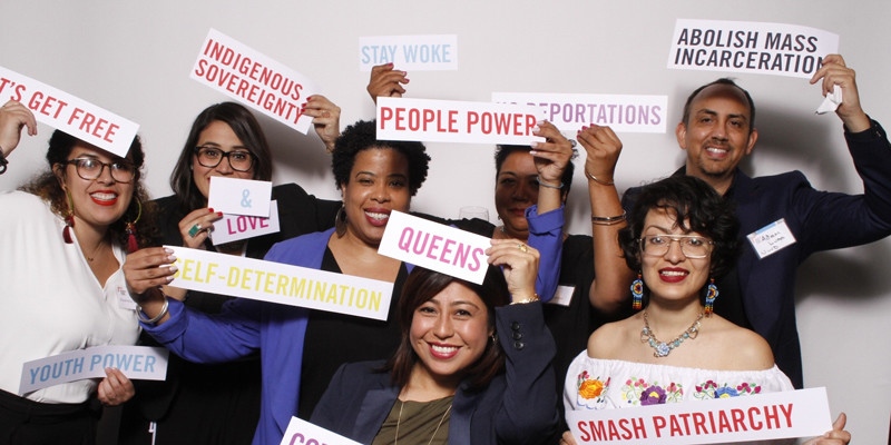 Seven leaders from United We Dream posing in the photobooth at our 2018 gala holding signs that include 'People Power,' 'Abolish Mass incarceration,' 'Stay Woke,' 'Youth Power,' and 'Smash Patriarchy'