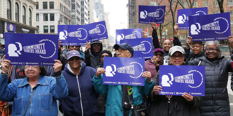 Members of Community Voices Heard standing on a NYC street holding signs with the CHV name