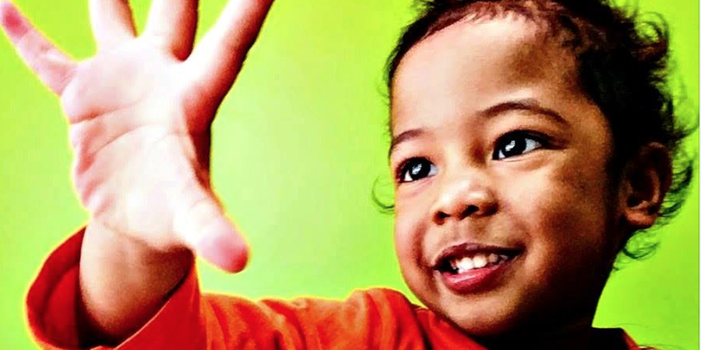 An African-American toddler with his hand reaching out