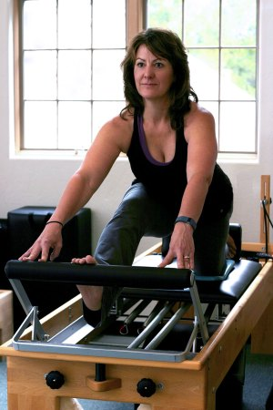 The author Kim Padilla working out on a Pilates Reformer at White Mountain Pilates Studio in Mt. Shasta. Photo by Audrianna Thompson.