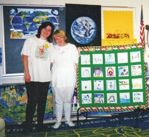 Tami Lavitt with Cindy McPherson stand by a quilt that Tami made from students' drawings to celebrate their love for their teacher who was in love with penguins