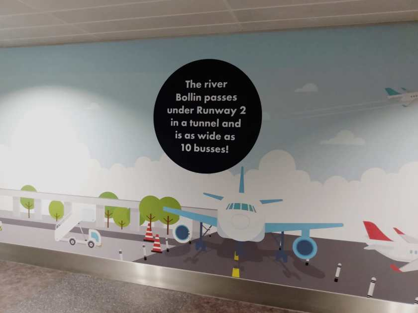 Poster at Manchester Airport showing planes and the text 'The river Bollin passes under Runway 2 in a tunnel and is as wide as 10 buses!'