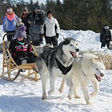 Youth riding on sled being pulled by two sled dogs while people watch in the background