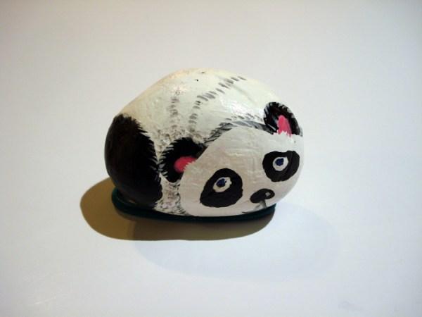 small stone painted like a black and white panda bear by Ping Yan