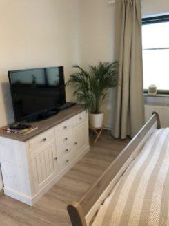Schlafzimmer mit Kommode und TV