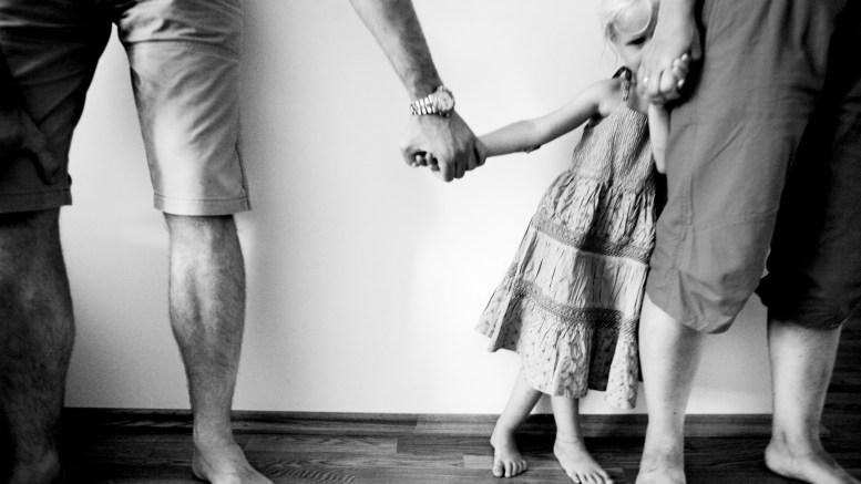 Little girl hand in hand with mom and dad. Love mom and dad.