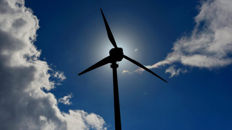 Vindturbin mot blå himmel. Skyer. A wind turbine is a device that converts kinetic energy from the wind, also called wind energy, into mechanical energy in a process known as wind power