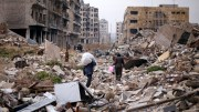 People walk amid the rubble as they carry belongings that they collected from their houses in the government controlled area of Aleppo