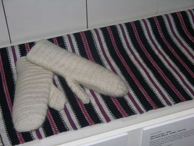 Elsa Eikås Bjerck was the first Norwegian instructor to teach weaving at Vesterheim. In 1978 she also taught weaving on a Vesterheim folk art tour to Norway. This piece replicates an early bed pillow from Jølster in Sogn, Norway, in plant-dyed wool on linen. The mittens were done in nålbinding, an ancient looping technique.