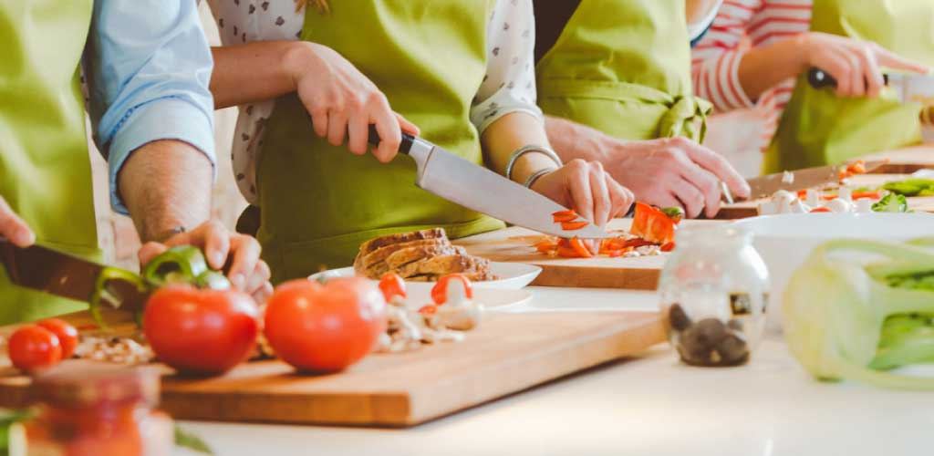 food class participants chopping ingredients with matching aprons at a counter