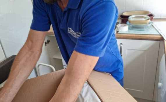 Martin, carefully wrapping some crockery on a house removal