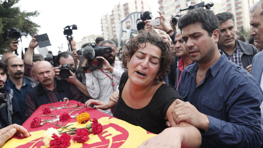 A relative mourns at the coffin of Korkmaz Tedik, executive member of the political party EMEP