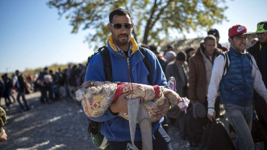 A refugee and his child on their way to Serbia, photo by AFP