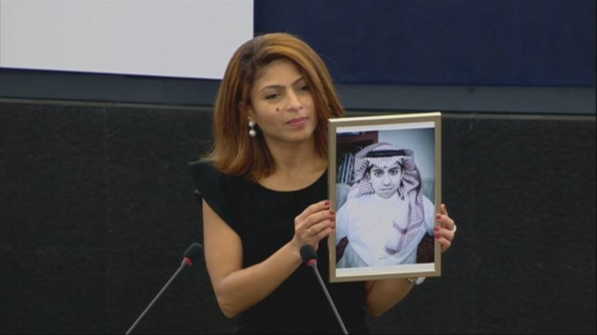 Saudi jailed blogger's wife accepts human rights prize, holding a portrait of her husband