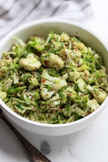 roasted cauliflower and brussels sprouts salad in a white bowl