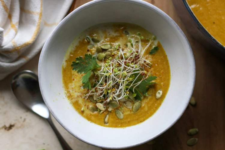 a white bowl full of curried cauliflower pumpkin soup with a spoon