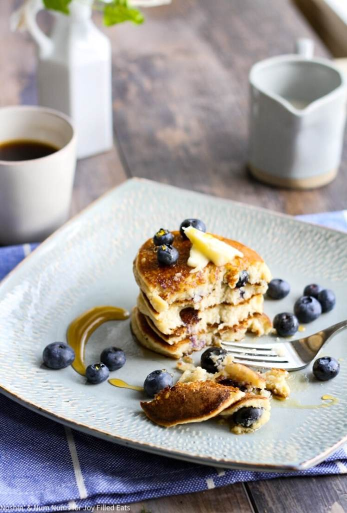 a half-eaten stack of lemon blueberry ricotta pancakes