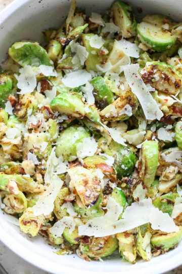 a white bowl filled with shaved lemon parmesan brussels sprouts