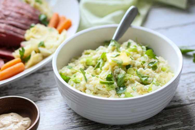 a white serving dish with cauliflower colcannon and a platter of corned beef and cabbage