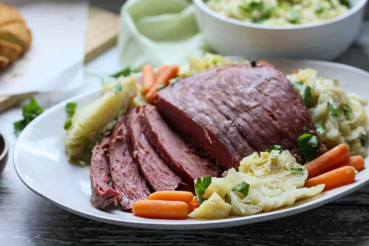 a white serving platter with sliced keto corned beef and cabbage