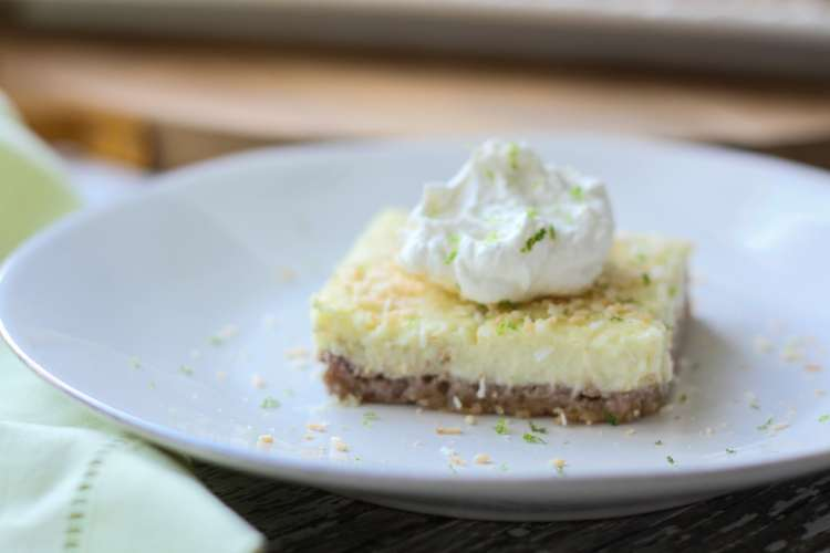 keto coconut lime bar topped with cream on a plate