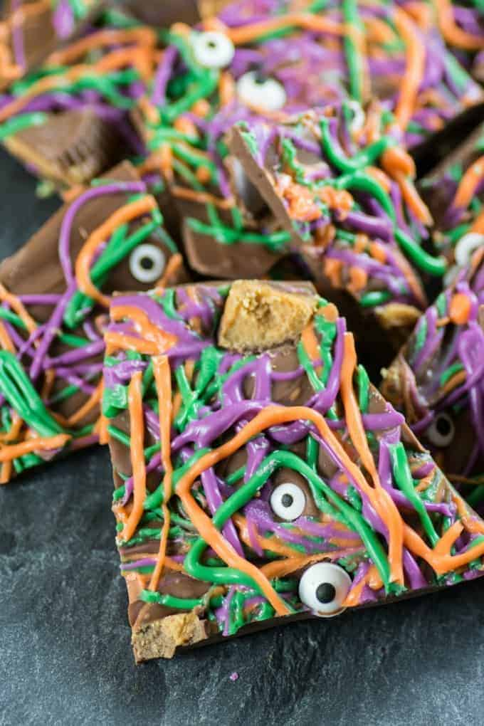 Purple, green and orange Halloween Bark with eyeballs and peanut butter cups on a slate board.