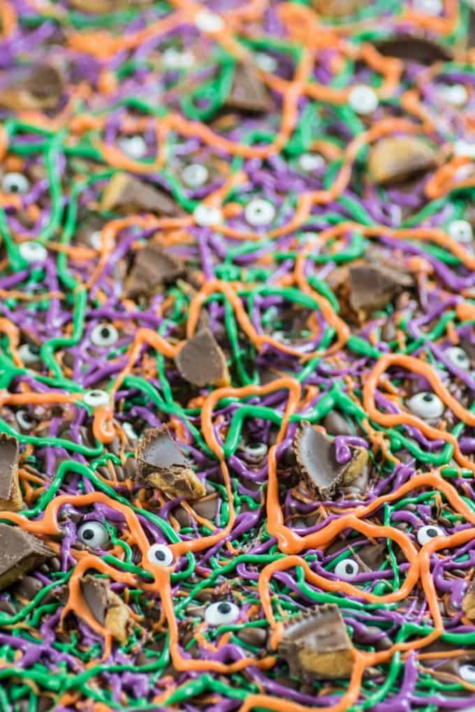 Purple, green and orange Halloween Bark with eyeballs and peanut butter cups