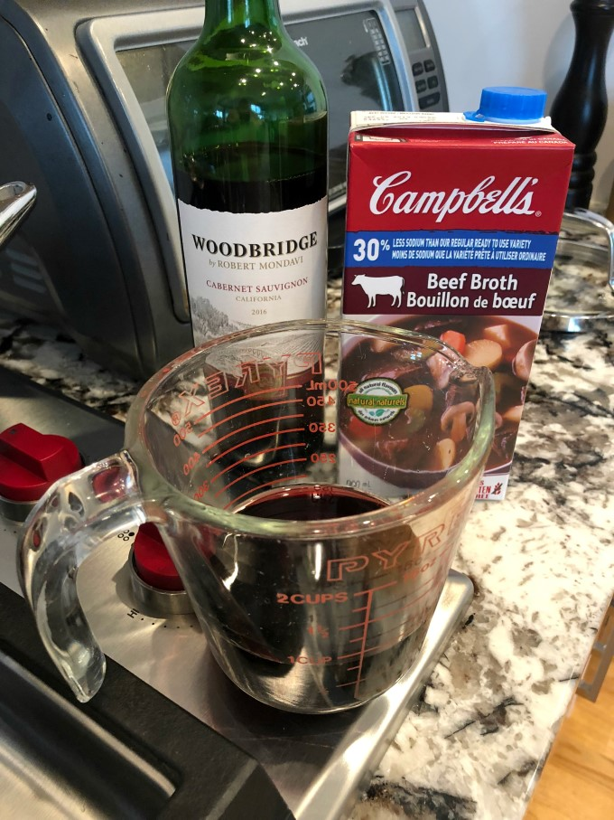 Measuring cup with red wine, bottle of Woodbridge by Robert Mondavi Cabernet Sauvignon and beef broth