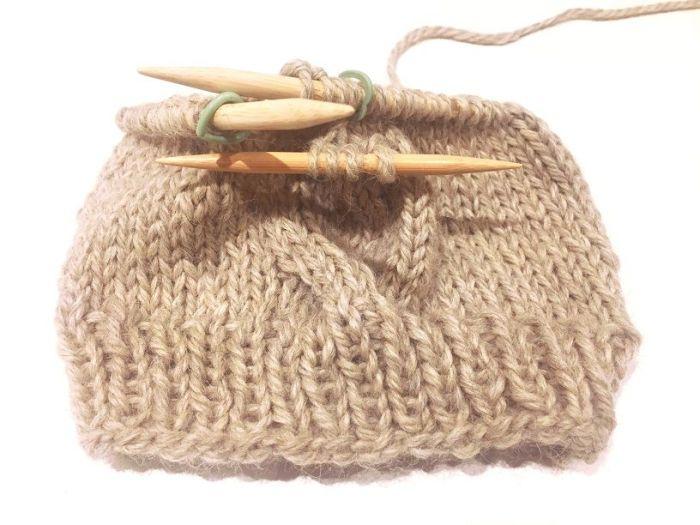 Cuello con trenza tejido a mano con agujas circulares.