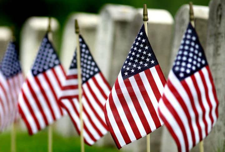 American flags next to veteran memorials
