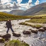 Juliette traverses the stone path across the river