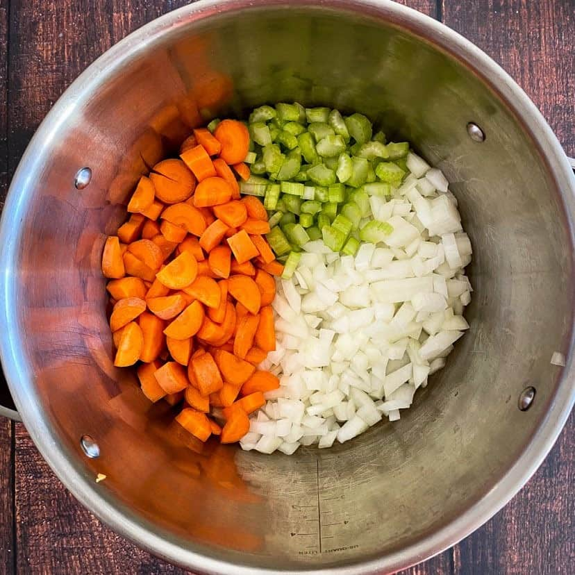 Cook down onion, celery, and carrots for the vegan potato soup.