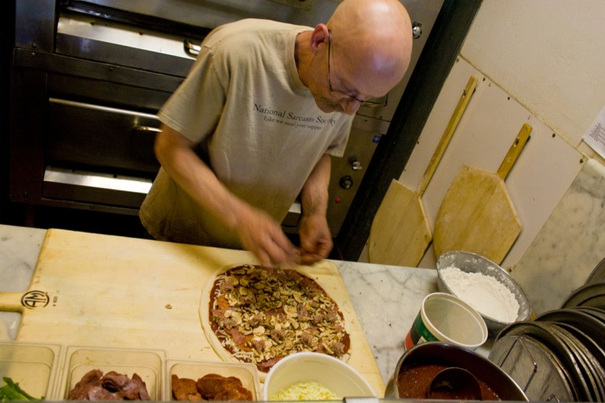 Mike topping the pizza
