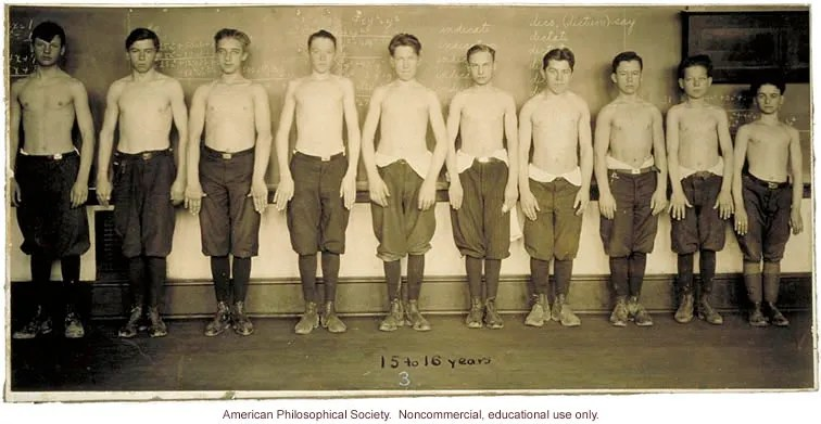 Sepia photograph, adolescent males standing in a line, in descending order of height, stripped to the waist, facing camera
