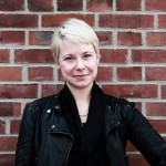 Alva Trabert facing camera, smiling, standing against brick wall. Wearing black leather jacket and black scarf. Short blonde hair.