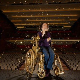 picture of Liz Carr on stage in a golden wheelchair rehearsing