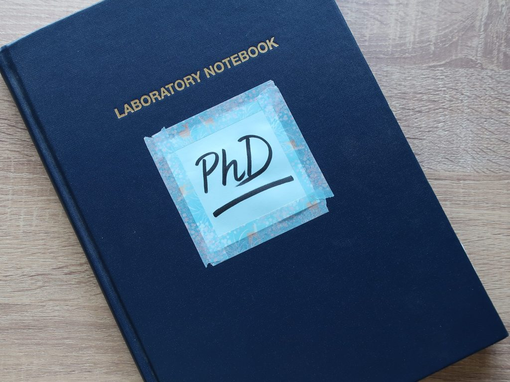A navy blue lab diary with a post-it note saying 'PhD' on the front.