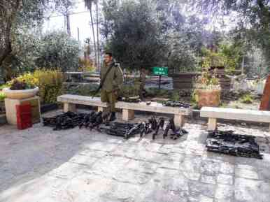 Young Israeli soldier guarding his comrades guns outside the Tomb of the Patriarchs on the Jewish side, Hebron, Palestine (2017-01-08)