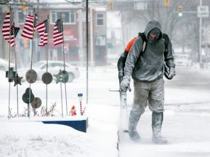 Mike Harring, of J & S Landscaping, blows snow off a sidewalk along Independence Street in Shamokin, Pa., on Wednesday, Jan. 30, 2019. Dangerous cold air is impacting a vast swath of the United States. (Larry Deklinski/The News-Item via AP)