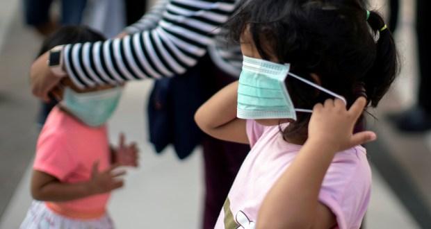 Criança colocando máscara covid
