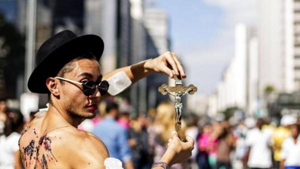 Homossexual exibe crucifixo católico em protesto contra cristãos