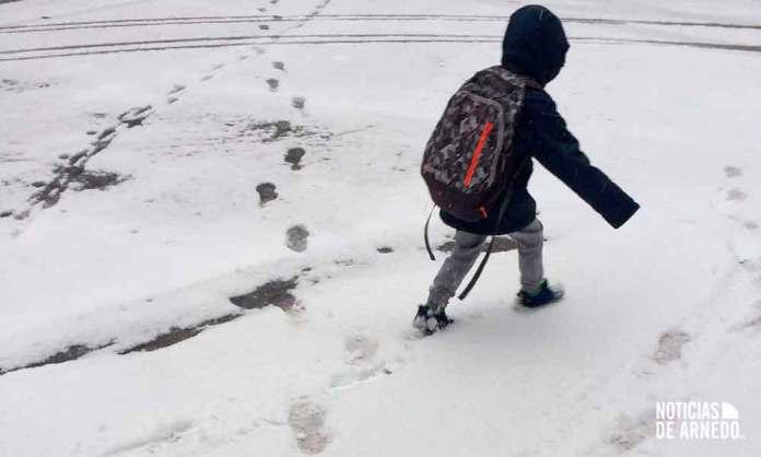 Un menor pasea por una calle nevada de Arnedo