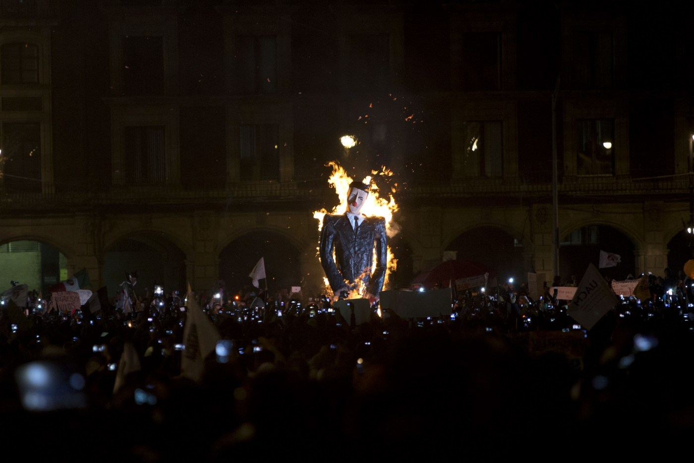 Una efigie que representa a Enrique Peña Nieto fue prendida en fuego durante una protesta masiva. Los manifestantes exigen justicia por los desaparecidos de Ayotzinapa.