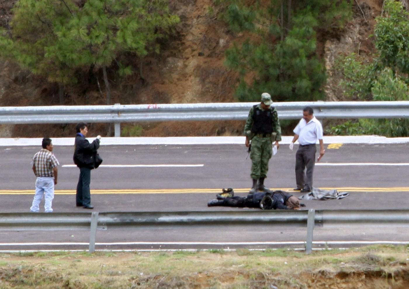 Investigadores forenses y militar investigan el lugar de los hechos.