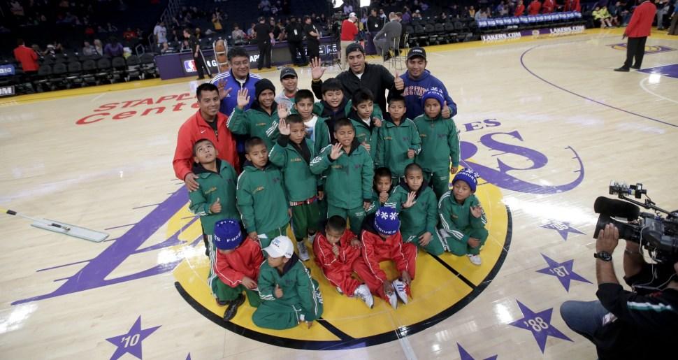 Miembros del equipo de básquetbol del equipo Triqui posan para una foto en la cancha de los Lakers de Los Ángeles.
