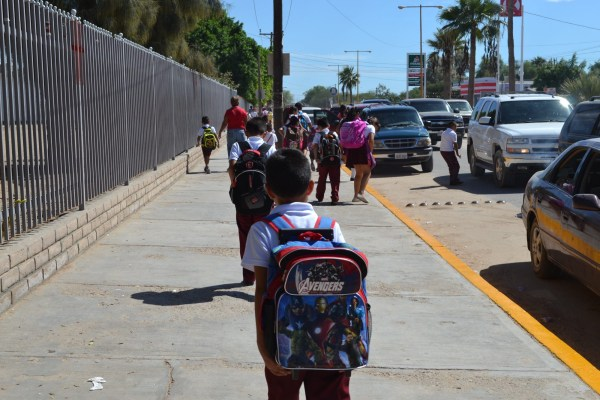 Niños con sus padres caminan a la escuela.