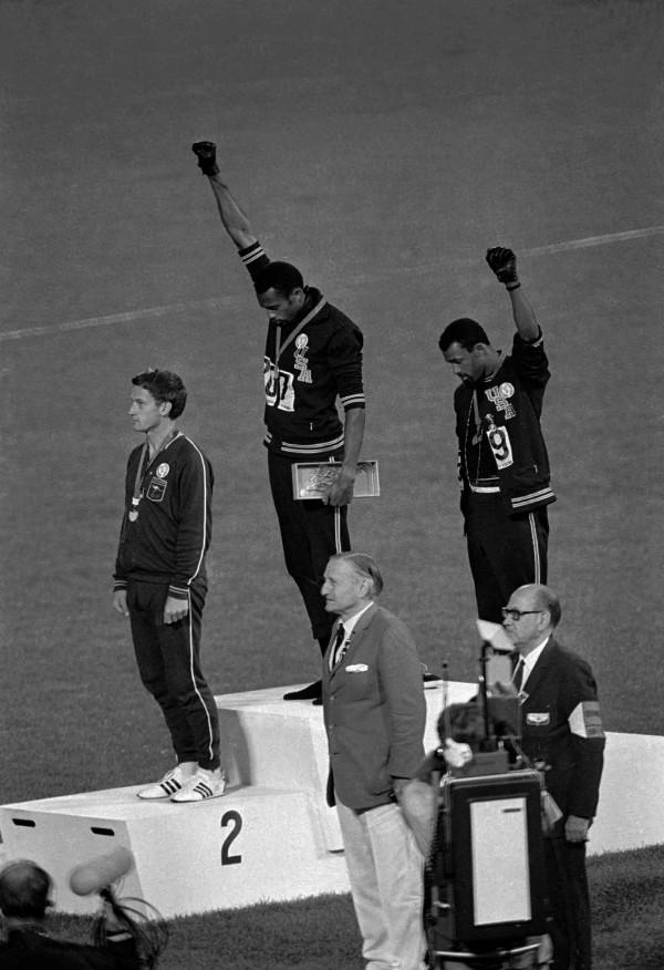 John Carlos y Tommie Smith, levantan el puño con guante negro.
