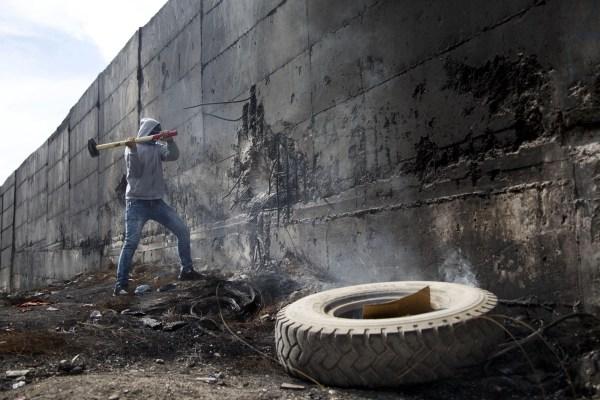 Un estudiante intenta romper el muro que separa Cisjordania e Israel
