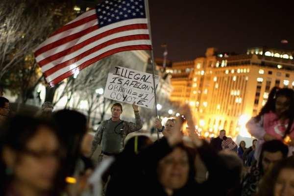 """Hombre en protesta se expresa contra Barack Obama con letrero que dice: """"¡[Ser] ilegal es un delito! Obama= Coyote #1"""""""